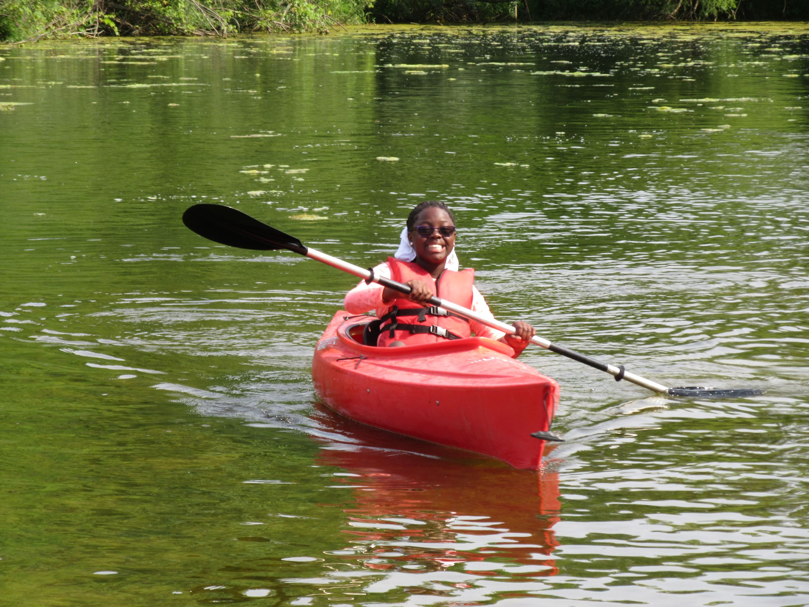 Girl kayaking on pond